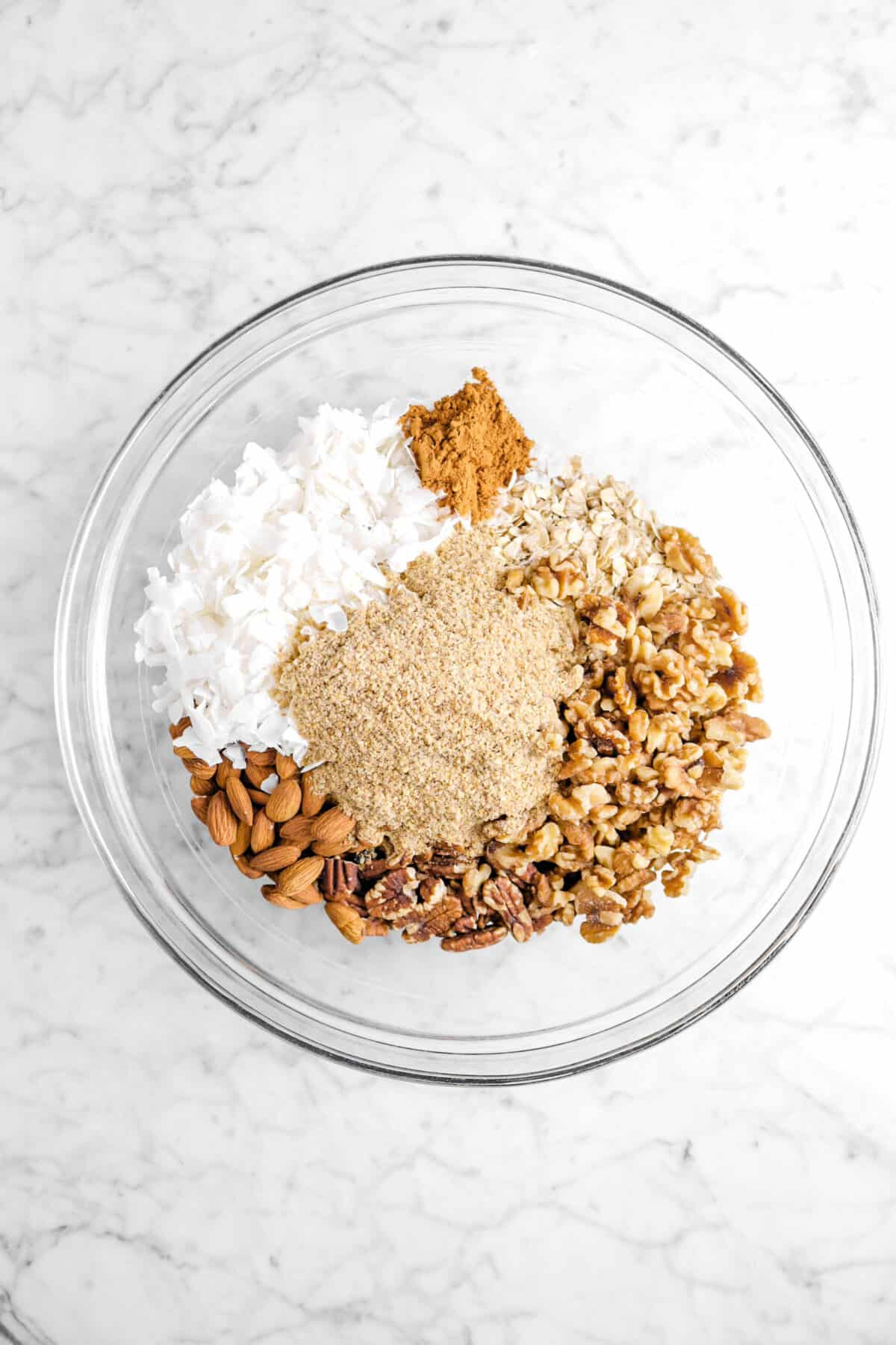 cinnamon, coconut, wheat germ, almonds, pecans, walnuts, and oats in glass bowl