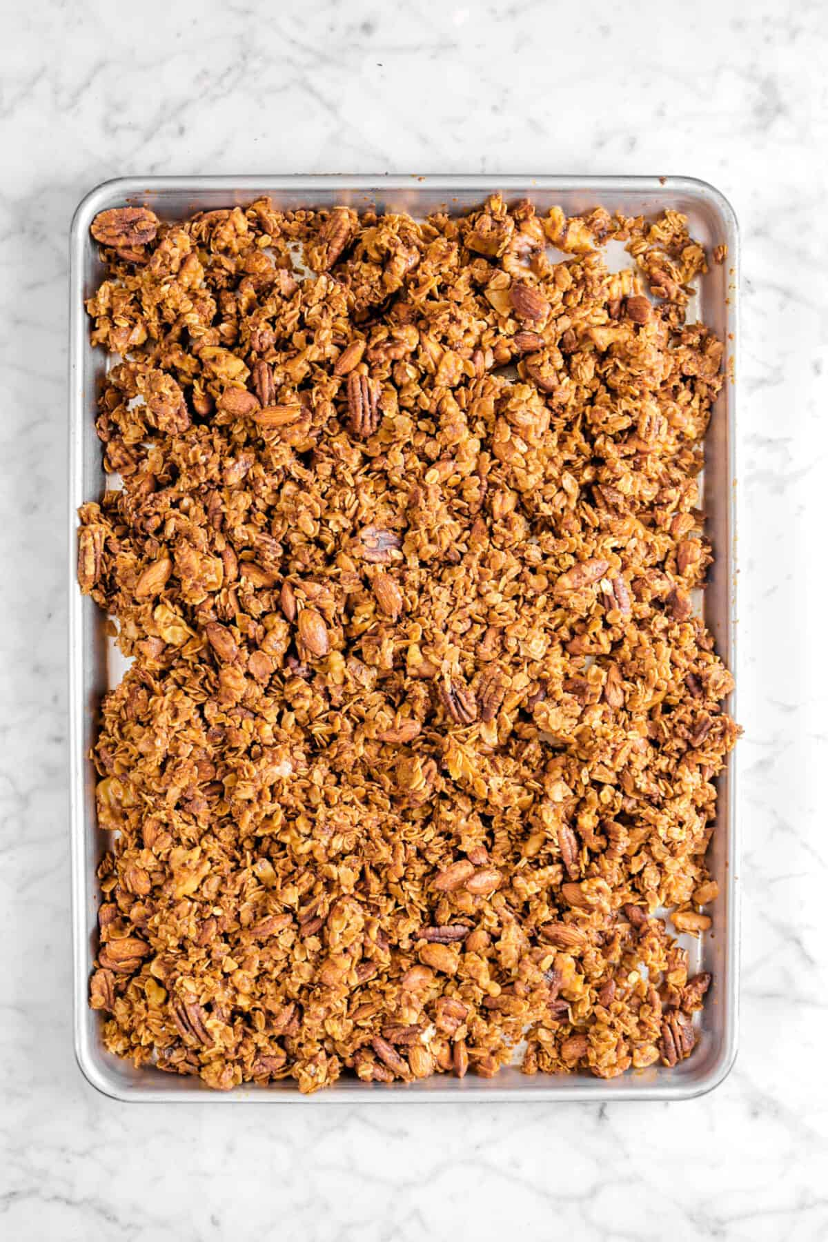 baked granola in sheet pan on marble counter