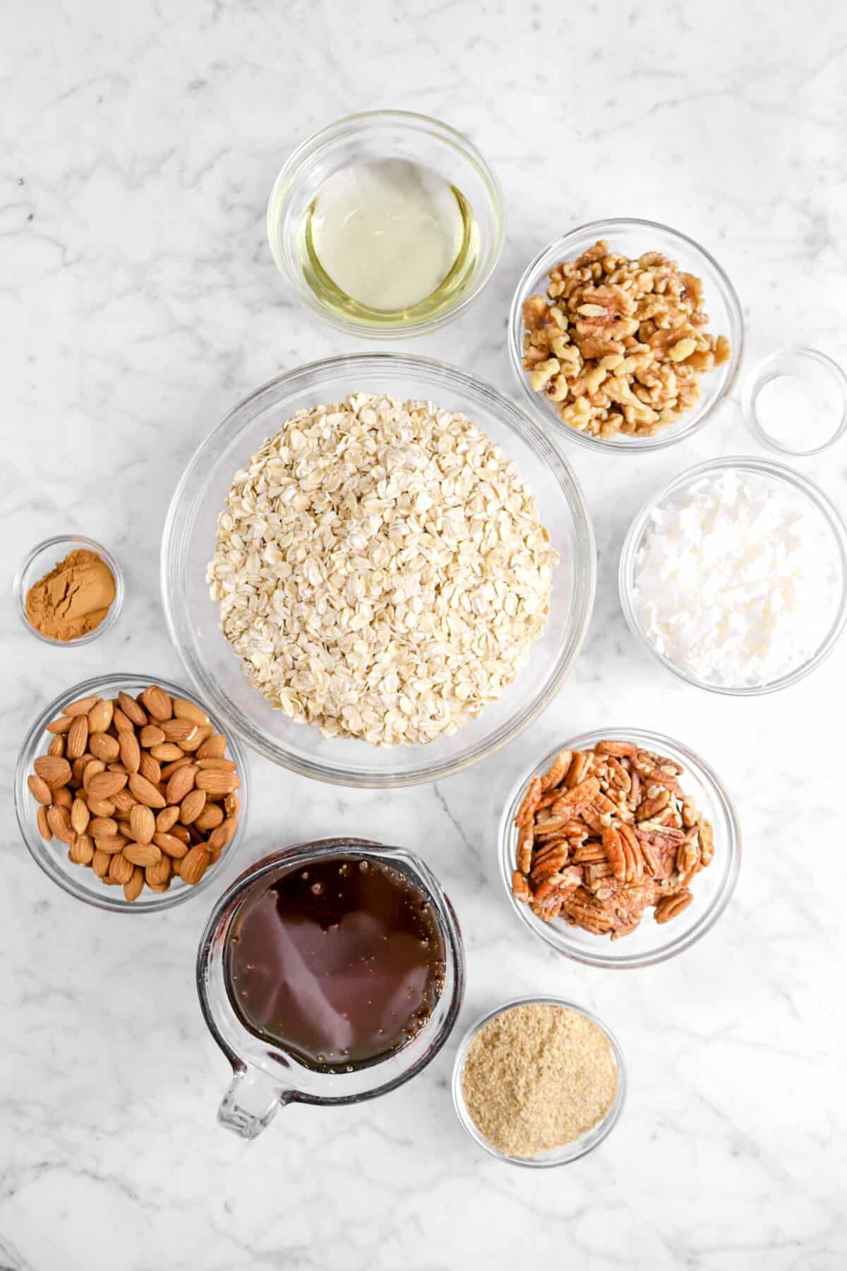 vegetable oil, walnut, salt, coconut flakes, pecans, oats, wheat germ, honey, almonds, and cinnamon in glass bowls