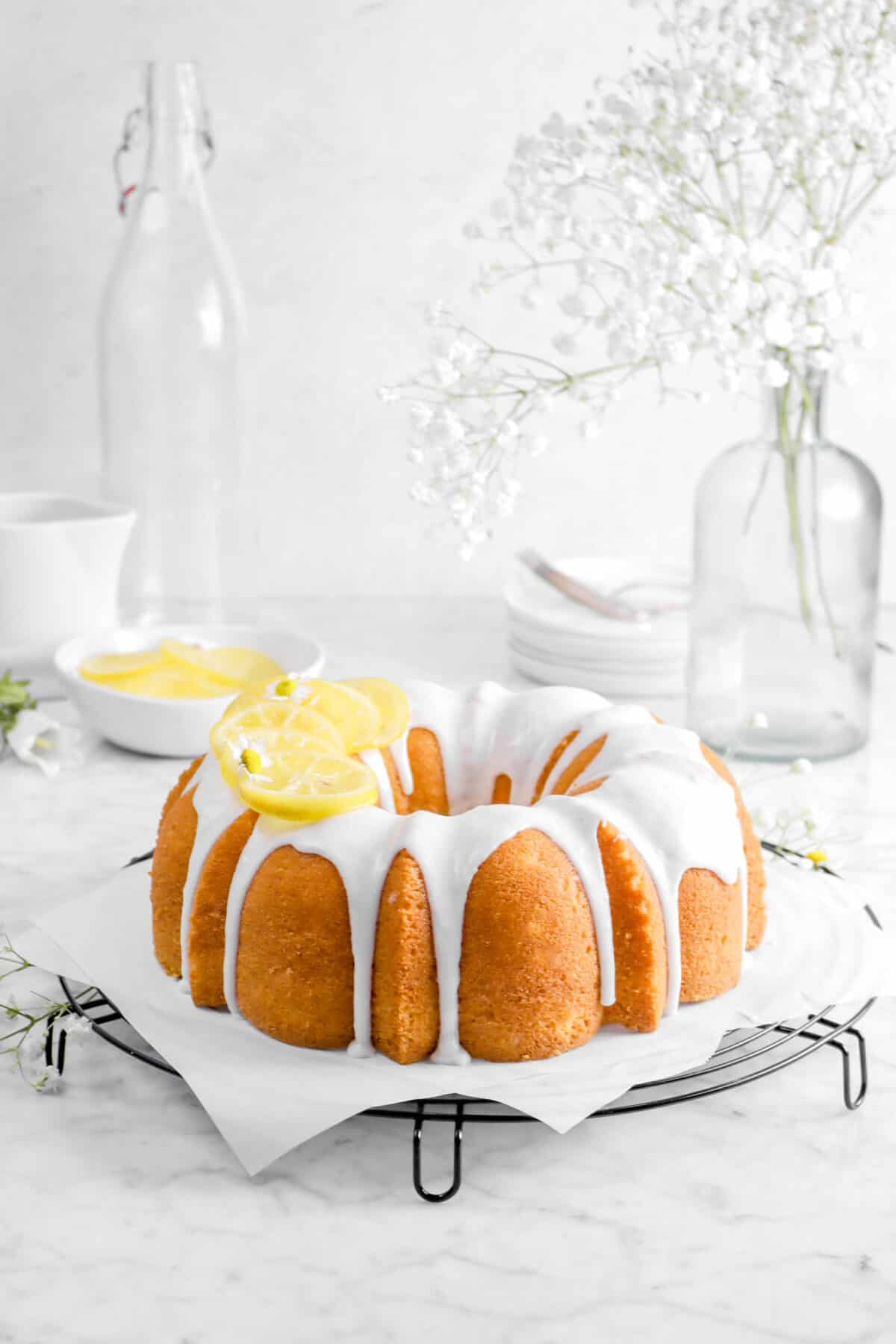 pound bundt cake with glaze, flowers, candied lemon, and plates behind