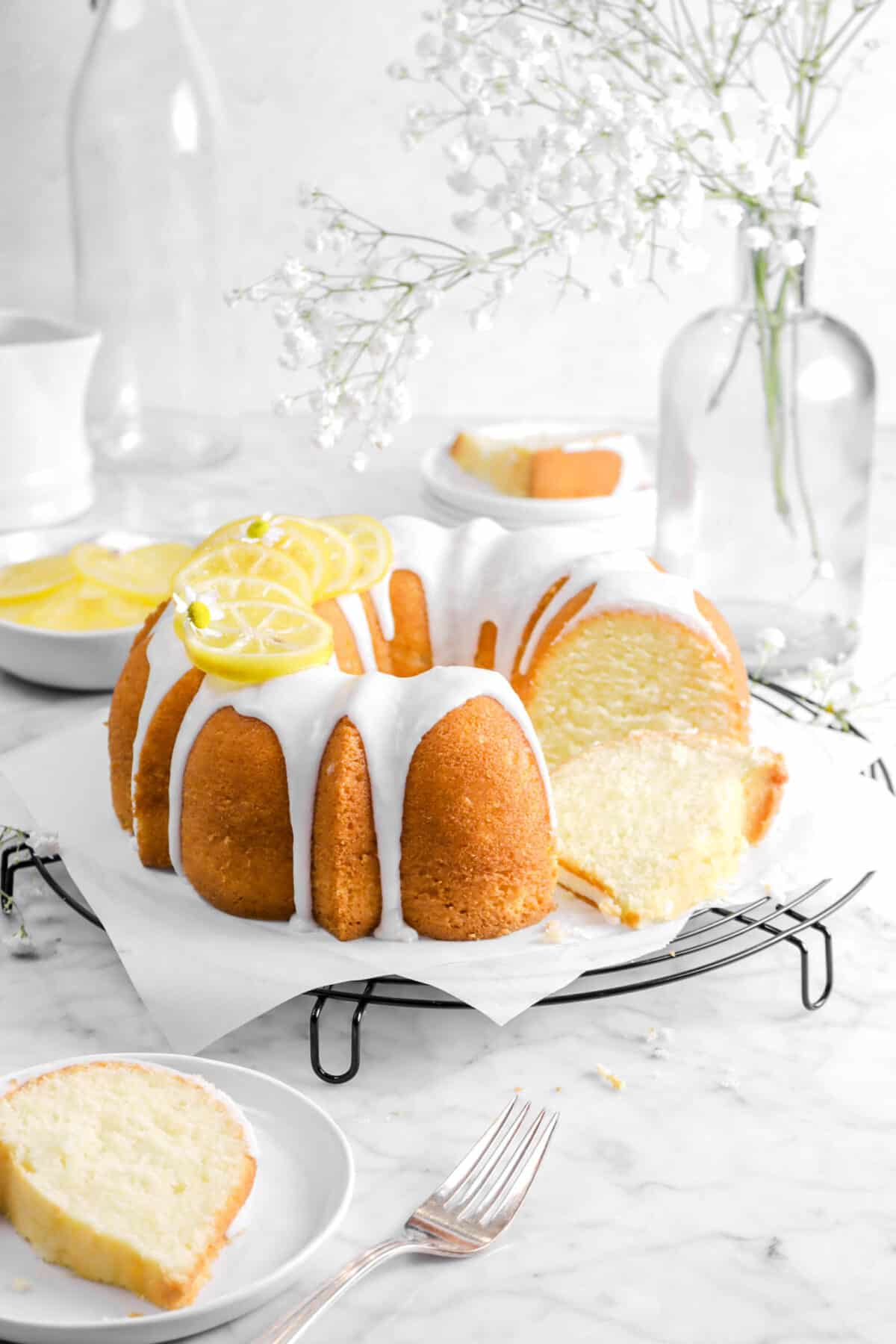 bundt cake on wire cooling rack with flowers, a slice in front, slice behind, and candied lemon slices