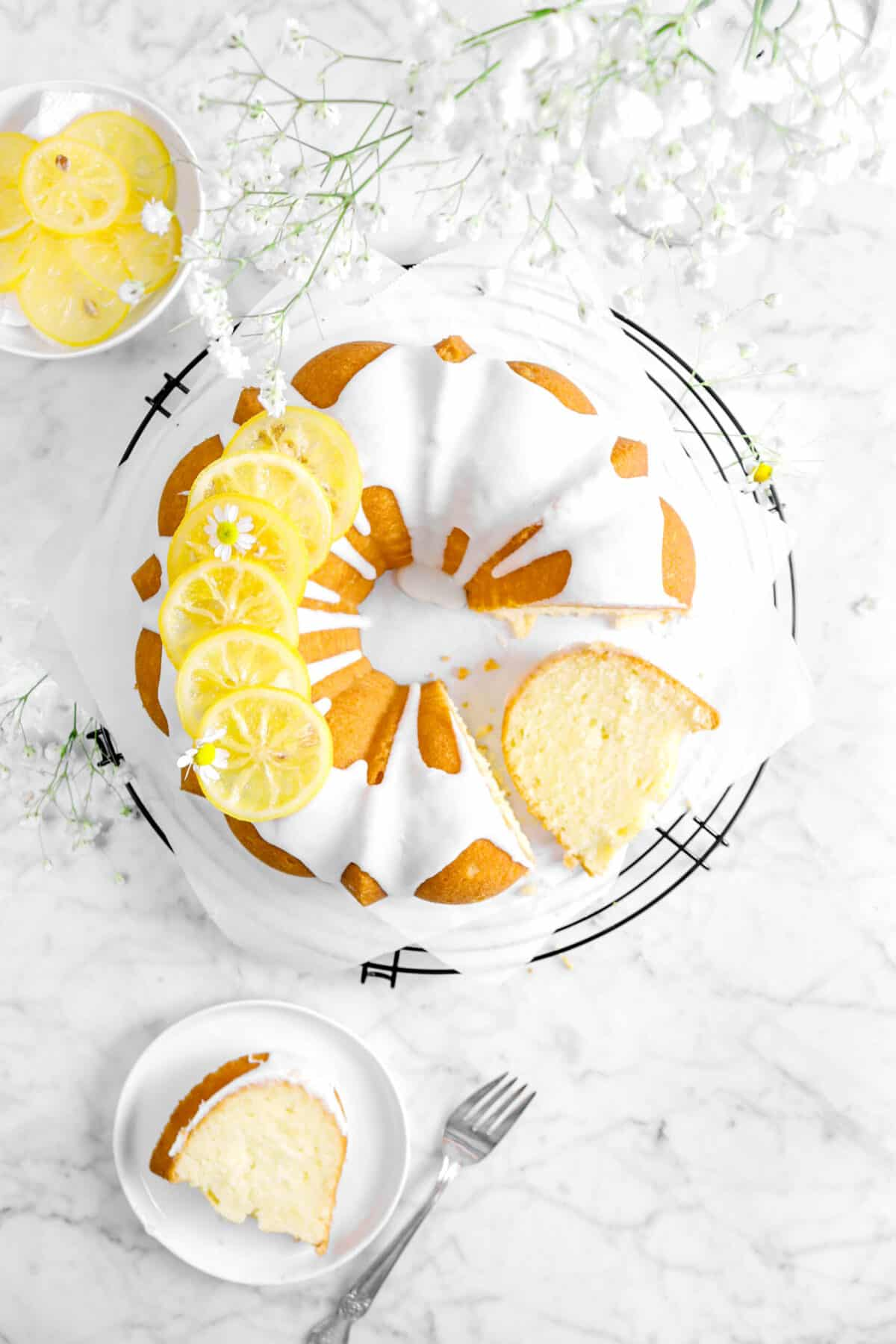 pound cake with candied lemon slices and glaze on top on a cooling rack with a slice on a white plate and slice on coolinf rack