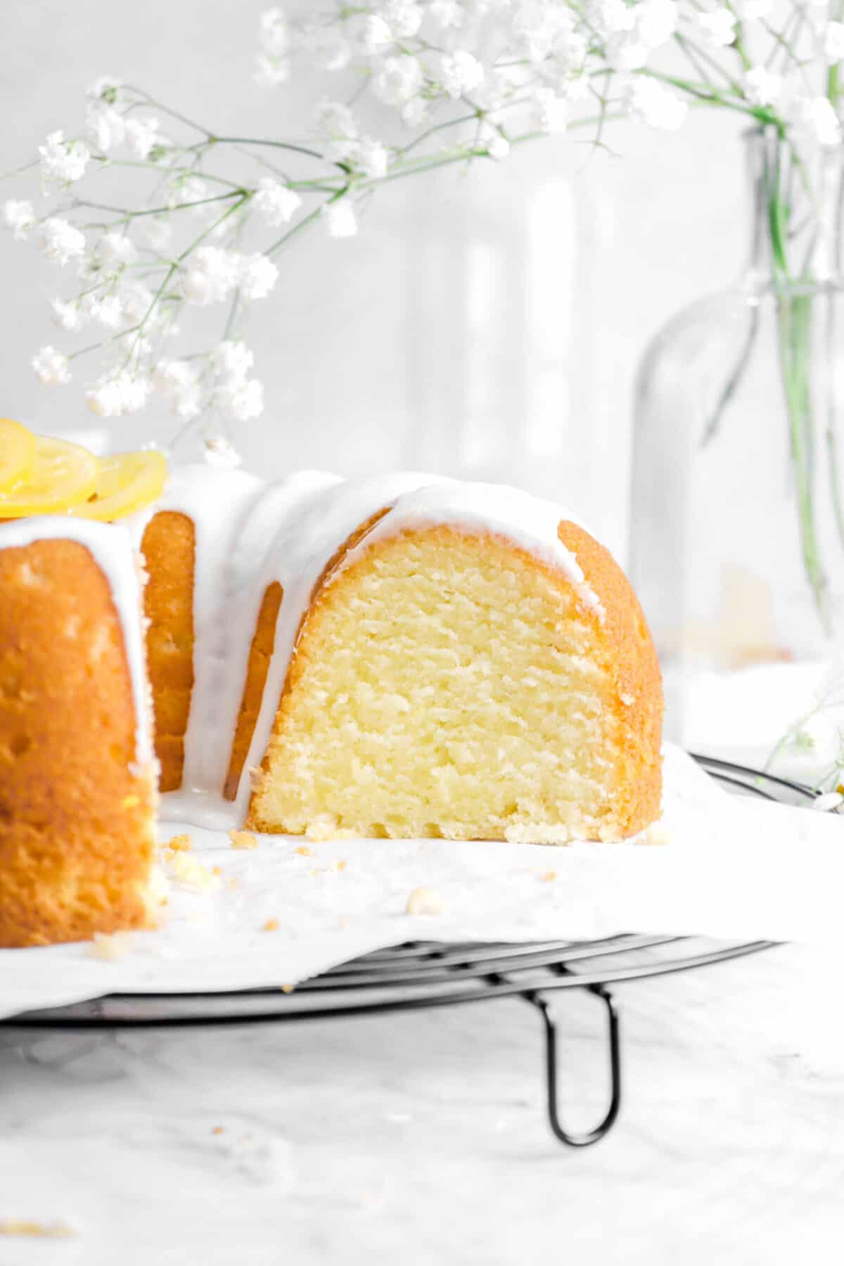 close up of lemon pound cake on cooling rack with flowers behind