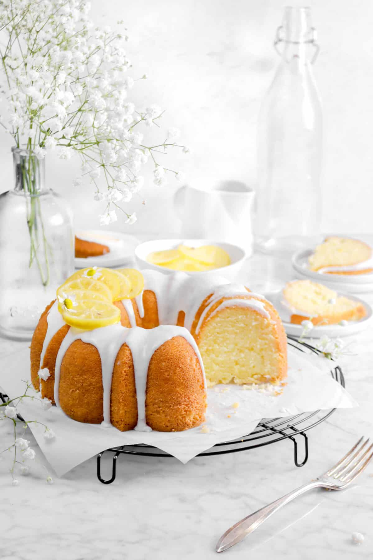 lemon pound cake with slices behind, candied lemon slices, and flowers with a fork