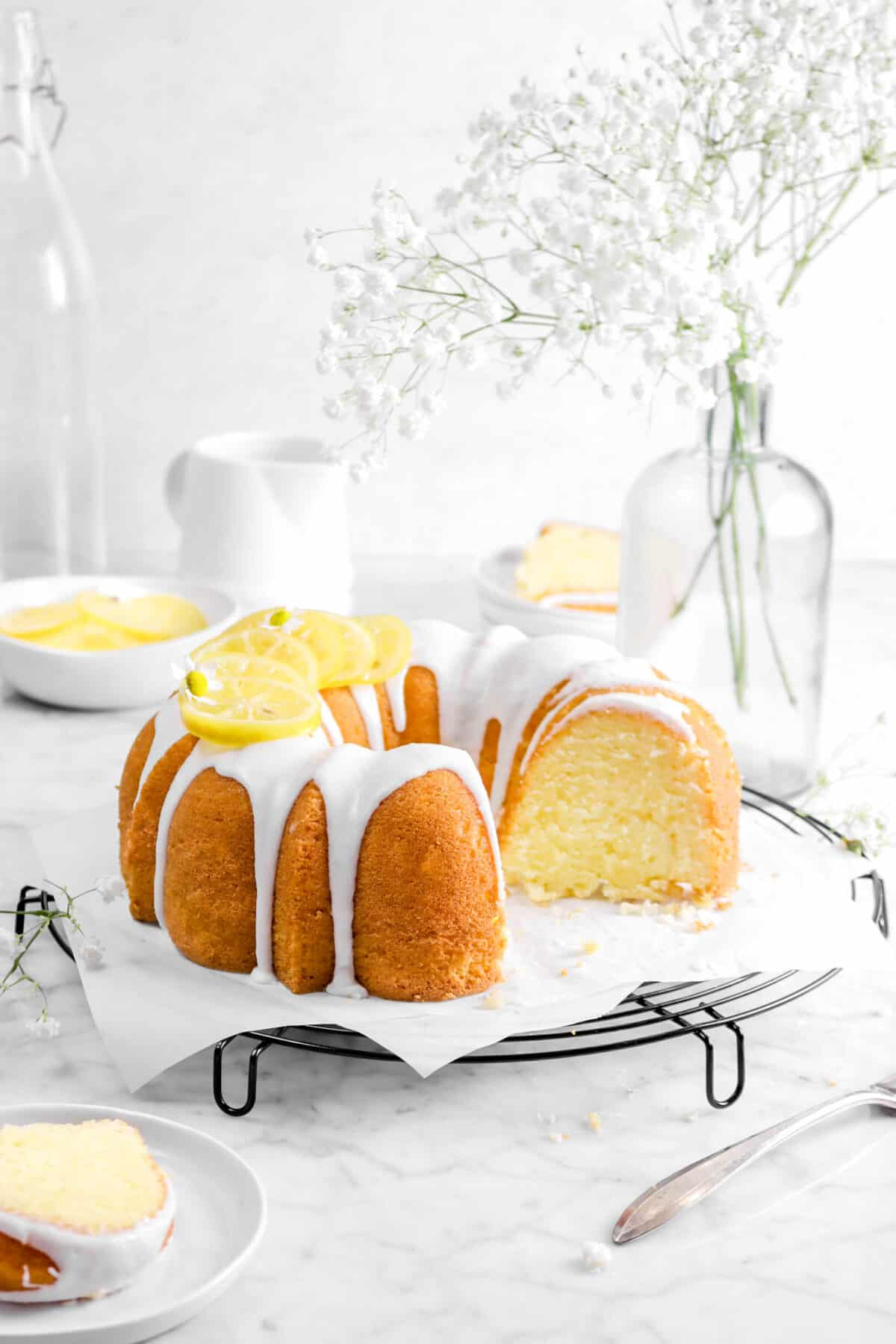lemon bundt cake with flowers, lemon slices, a fork, and slices of cake in front and behind