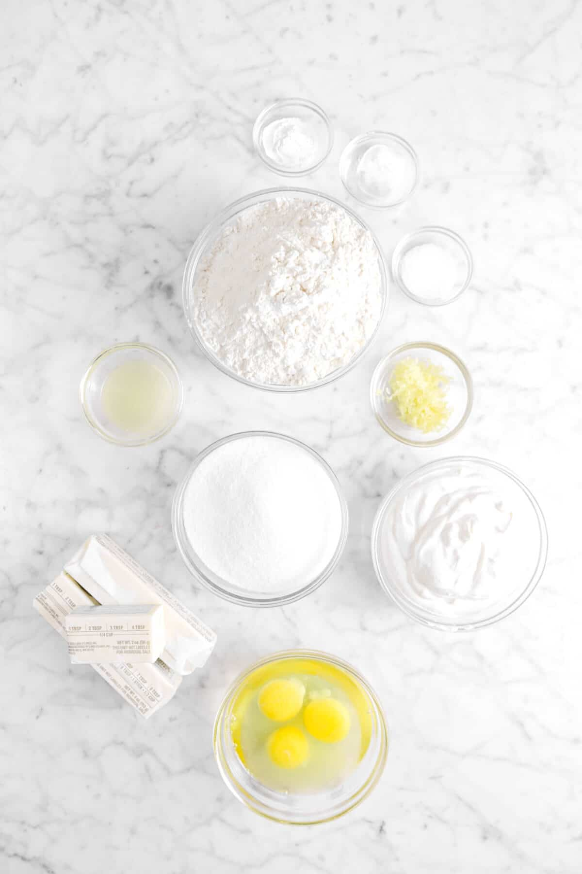 baking powder, salt, baking soda, flour, lemon zest, lemon juice, sour cream, sugar, butter and eggs on marble counter