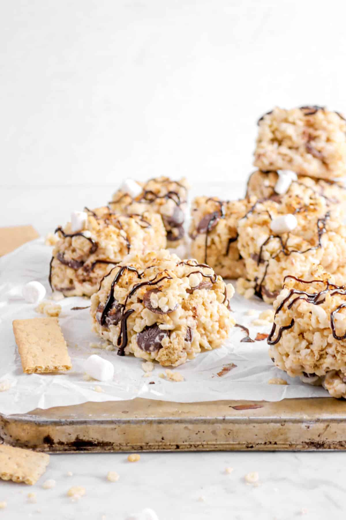 rice krispie treats on baking sheet with parchment, marshmallows, and graham crackers