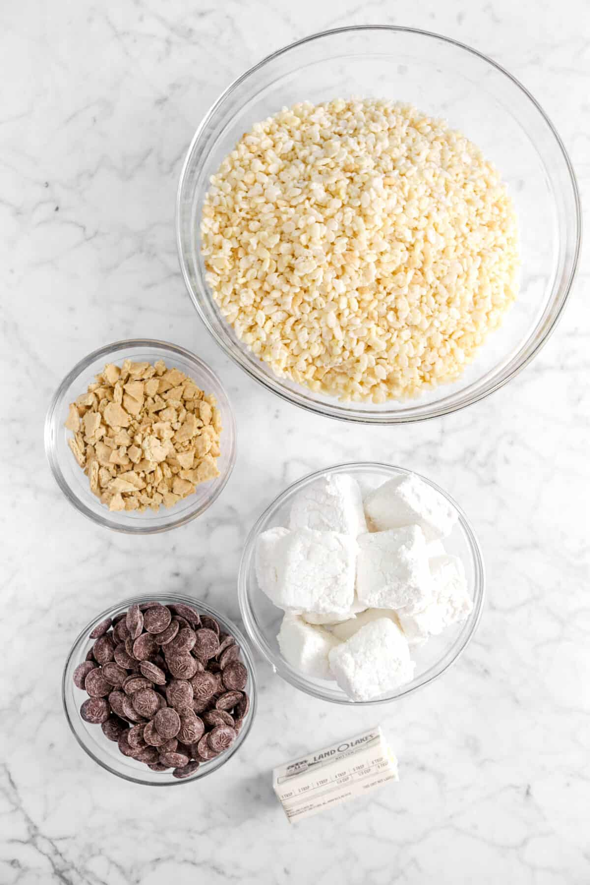 rice krispies, graham crackers, marshmallows, chocolate chips, and butter on marble counter