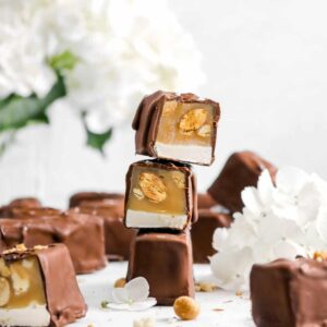 three stacked snickers with more around and hydrangeas behind