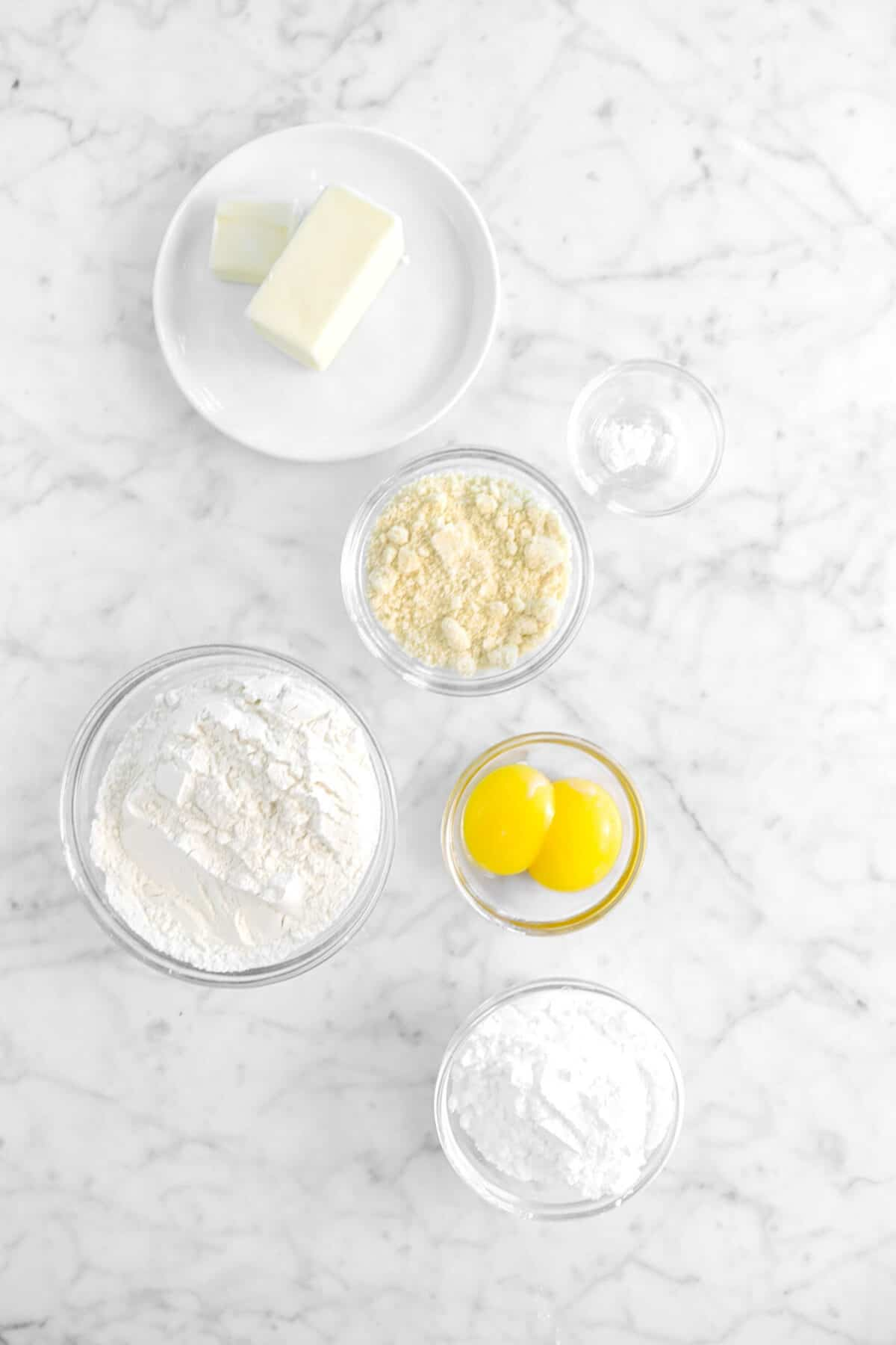 butter, almond flour, baking soda, eggs, flour, and powdered sugar on marble counter