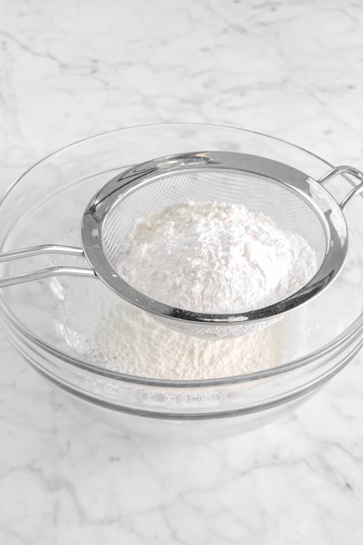 flour and sugar in sieve over glass bowl