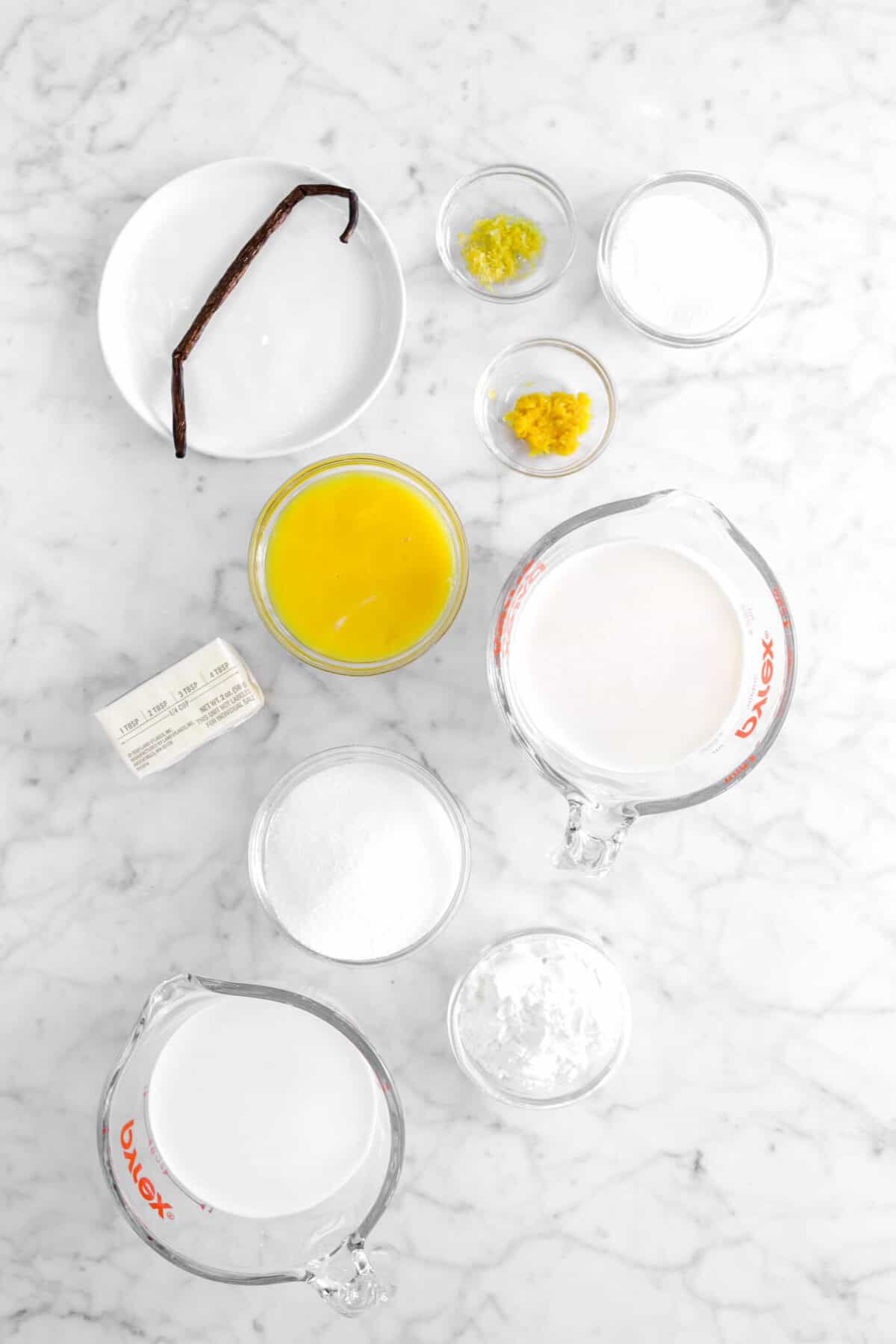 vanilla bean, orange zest, grapfruit zest, sugar, egg yolks, milk butter, corn start, and cream on marble counter