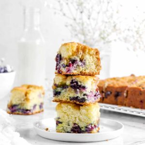 three stacked slices of blueberry buckle on white plate with flowers, glass of milk, and more cake behind
