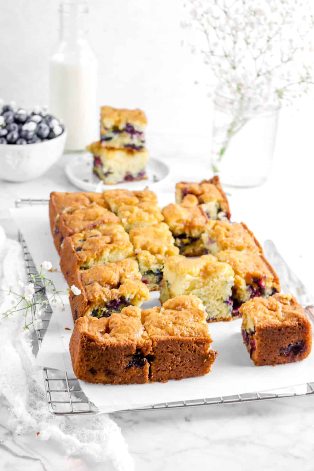 blueberry buckle sliced on wire cooling rack with flowers, two slices of cake, glass of milk, and bowl of blueberries behind
