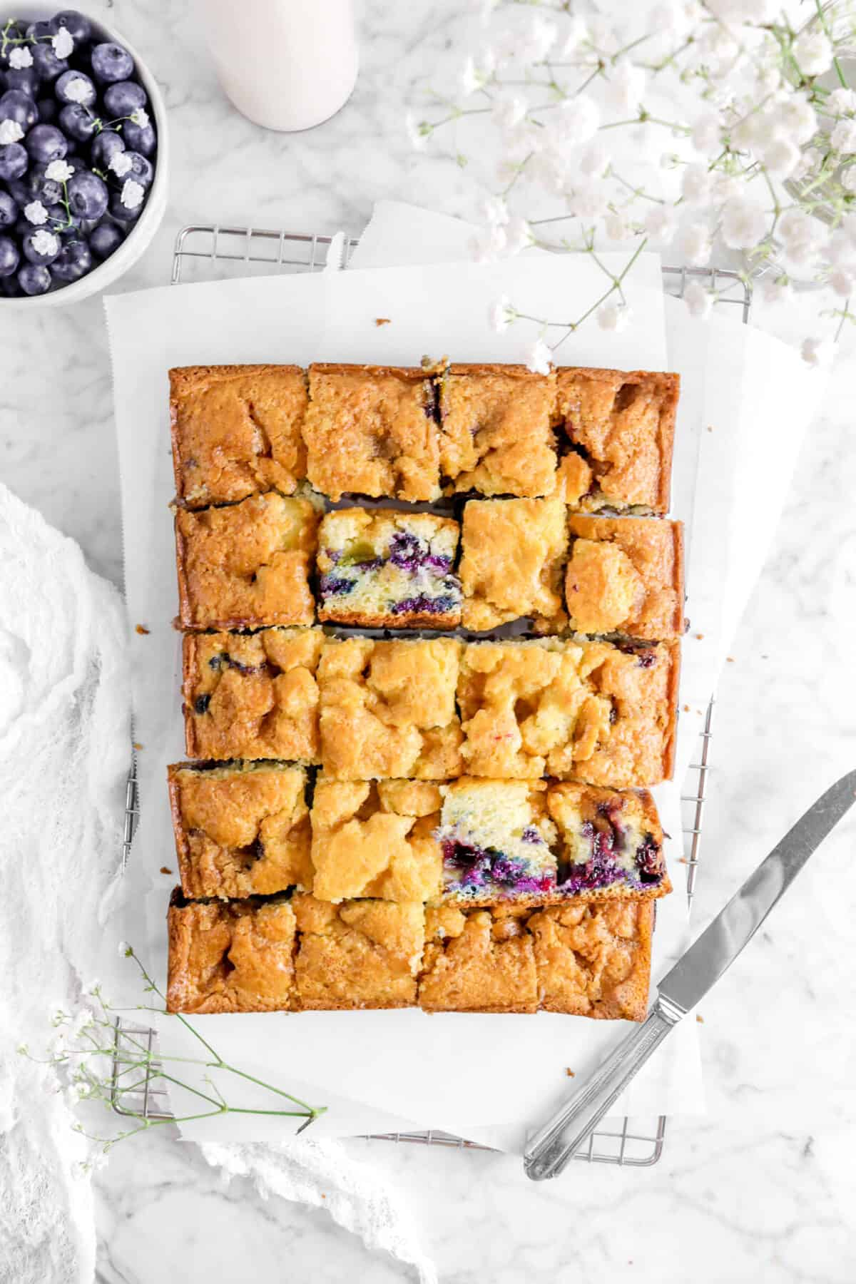 overhead shot of blueberry buckle on wire cooling rack with flowers, three sliced turned on their side, blueberries and a knife