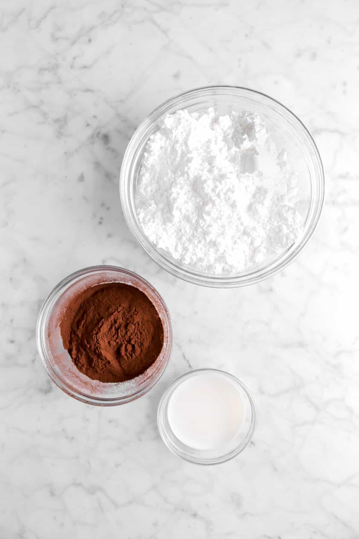 powdered sugar, cocoa powder, and milk in glass bowls