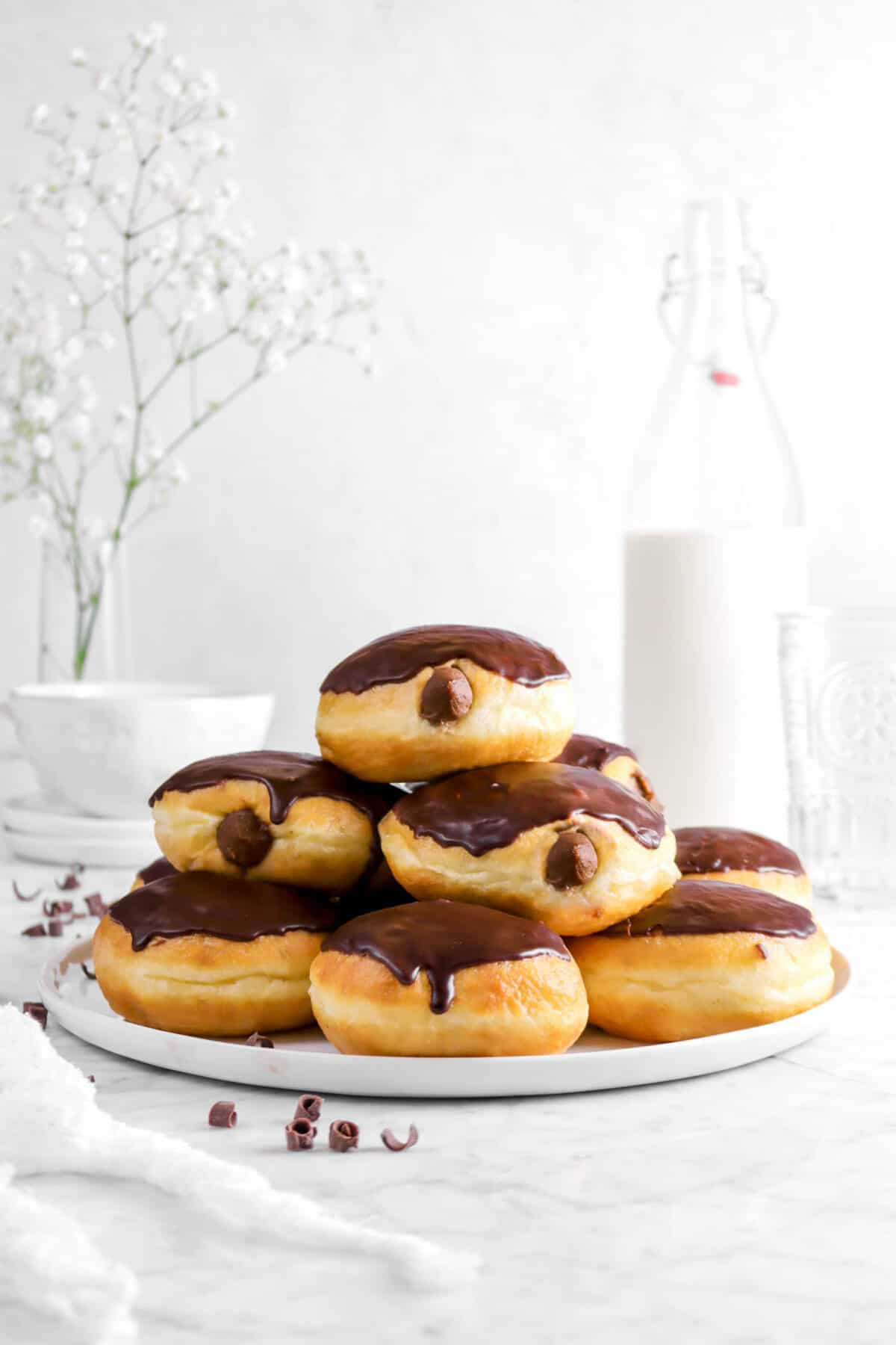doughnuts stacked on a white plate with milk, a glass, plates, and flowers behind