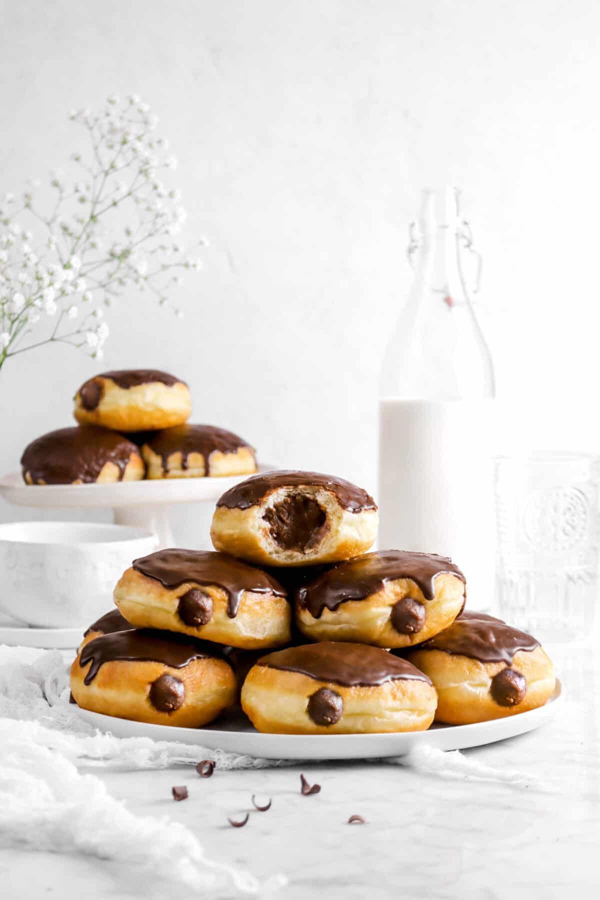 stacked chocolate filled doughnuts with milk behind, a cake stand of doughnuts, and flowers