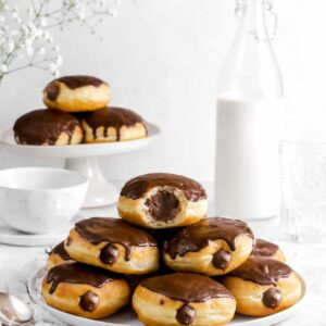 plate of stacked chocolate filled doughnuts with milk glass, coffee mug, stacked doughnuts, and spoons