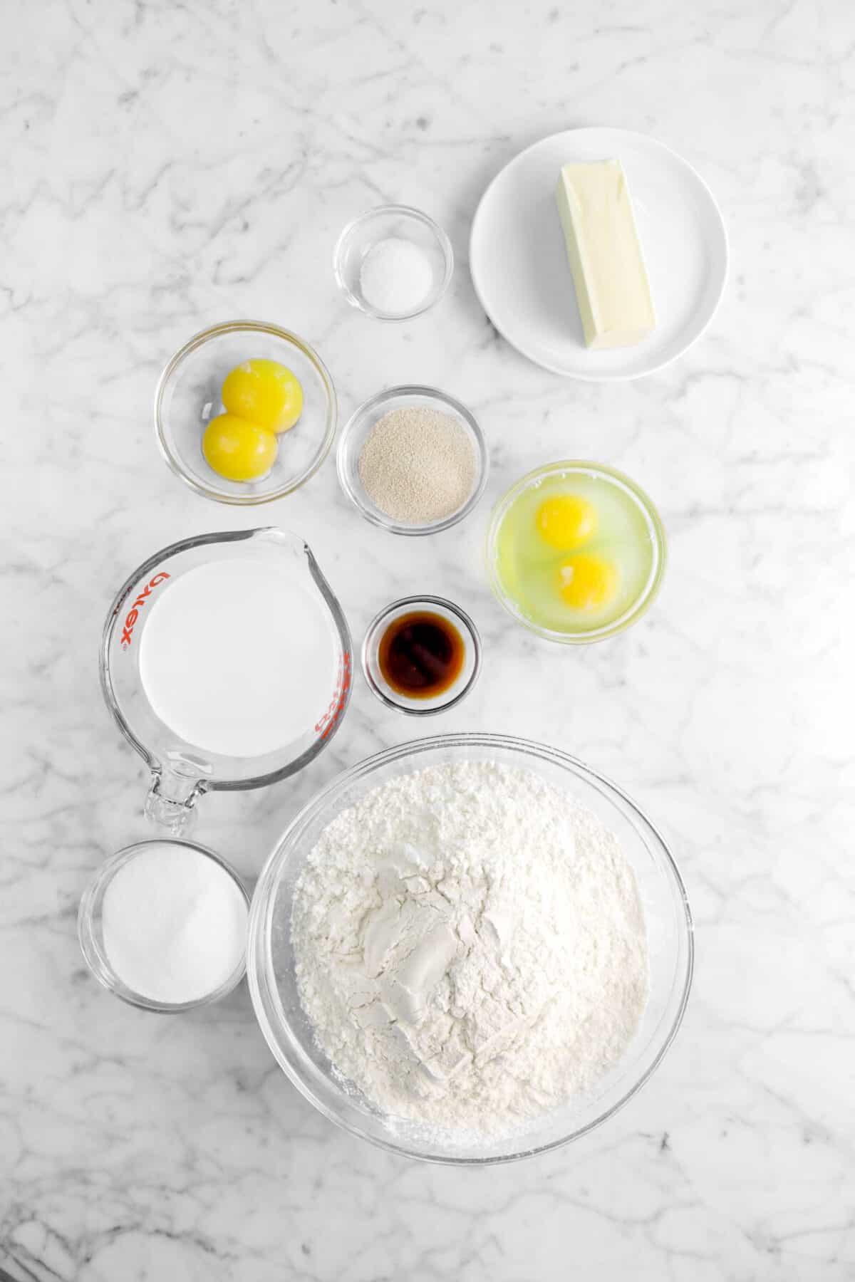 butter, salt, yeast, egg yolks, eggs, vanilla, milk, sugar, and flour on a marble counter