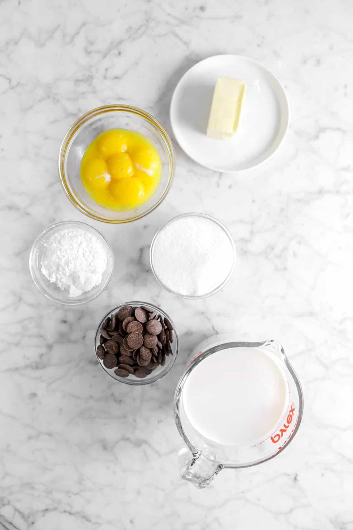 butter, egg yolks, sugar, corn starch, chocolate chips, and milk on marble counter