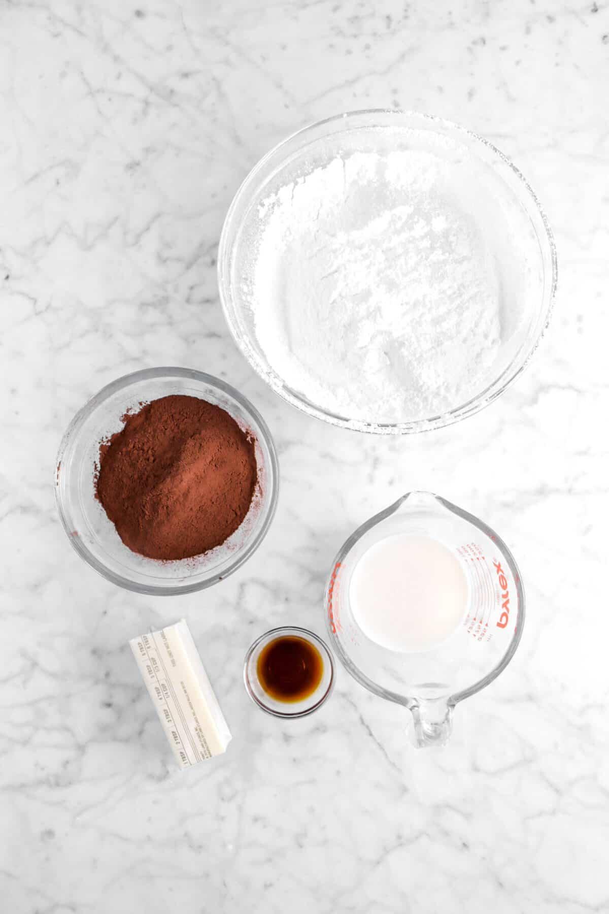 powdered sugar, cocoa powder, milk, vanilla, and butter on marble counter