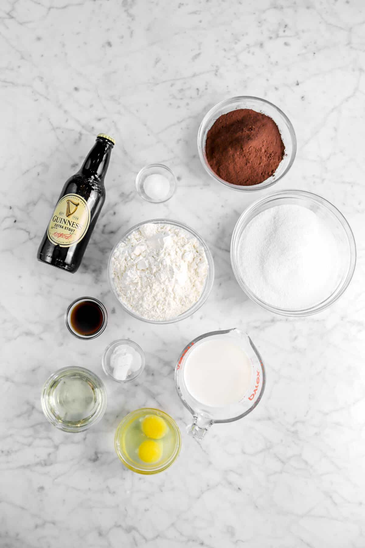cocoa powder, salt, sugar, flour, beer, vanilla, baking powder, milk, eggs, and vegetable oil on marble counter