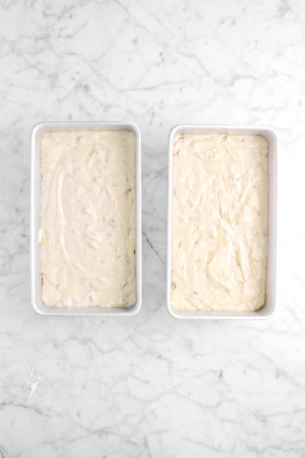 banana bread batter in two loaf pans on marble counter
