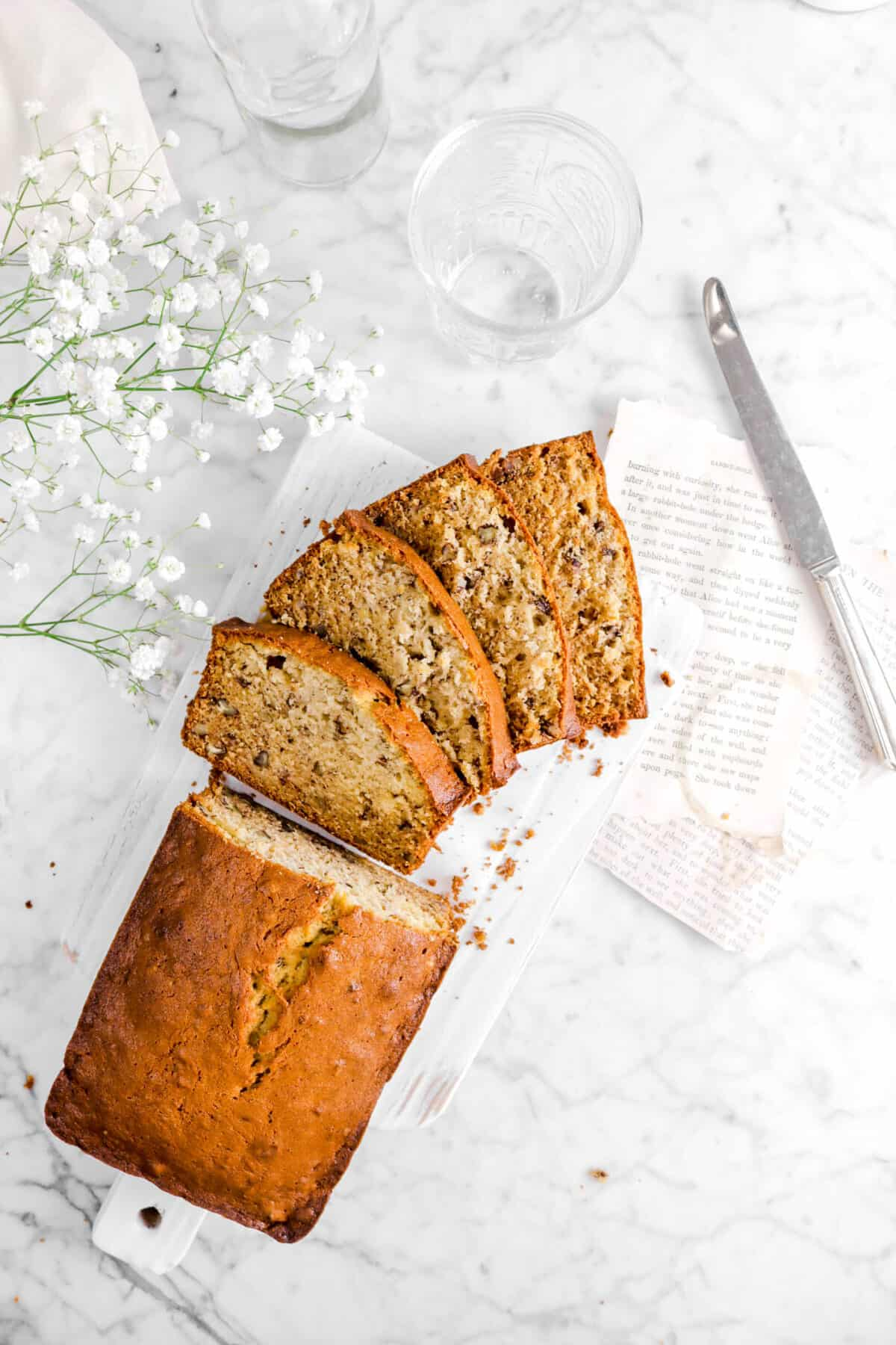 overhead shot of banana bread with four slices laying in front with flowers, glasses, a knife, and book pages
