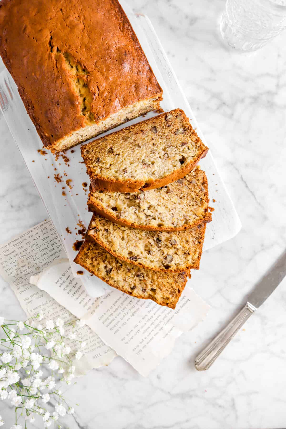banana bread on white board with book pages and flowers