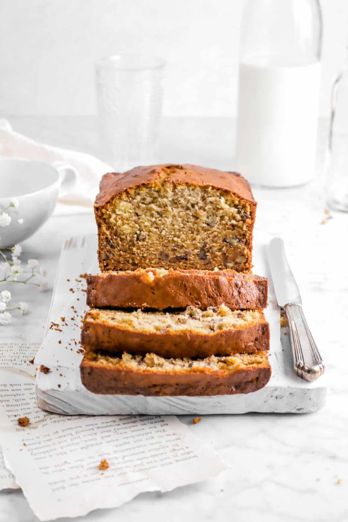 four slices of bananabread with loaf behind on white board with knife, napkin, and milk