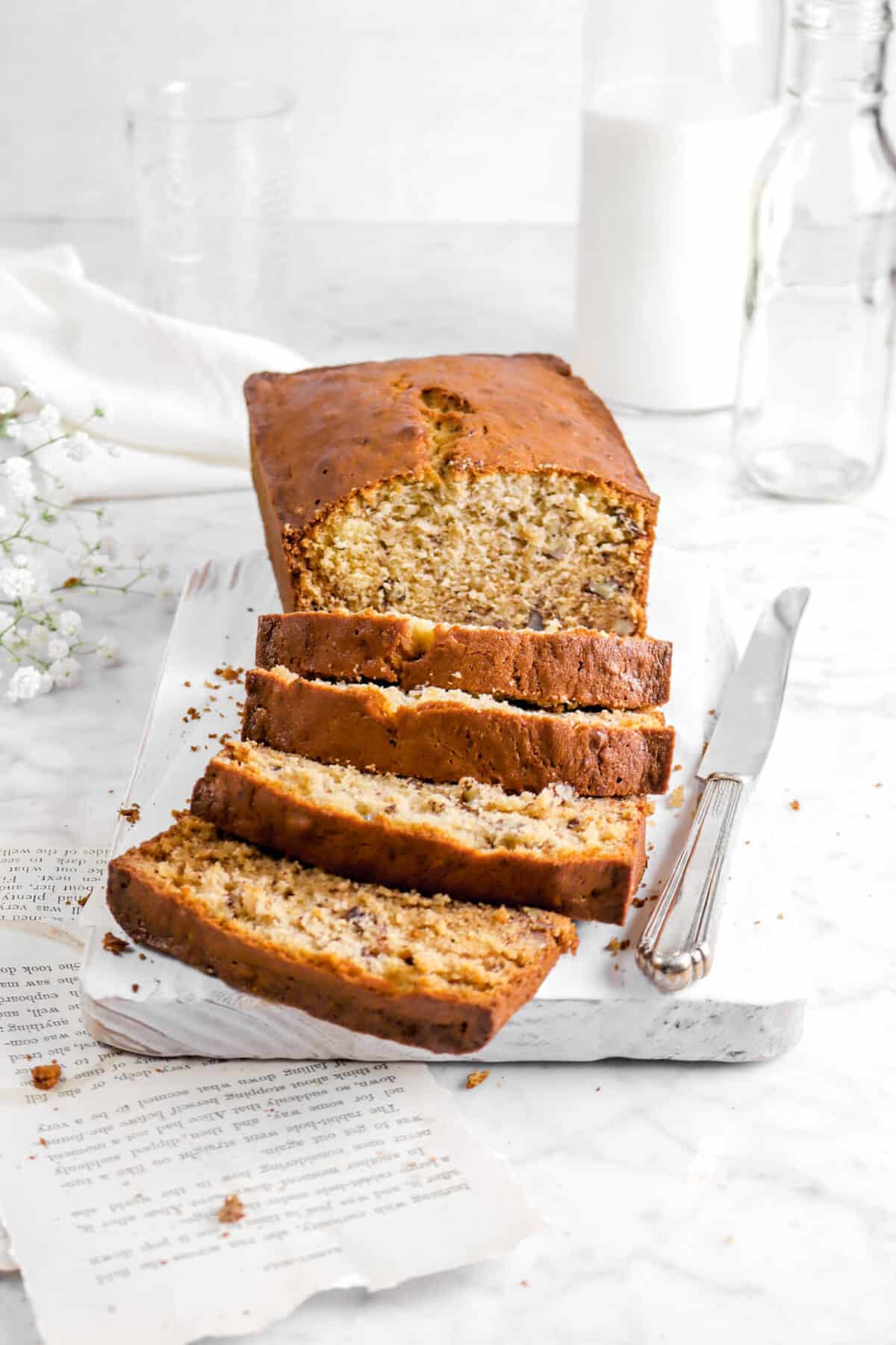 banana bread with four slices in front on white board with knife and book pages