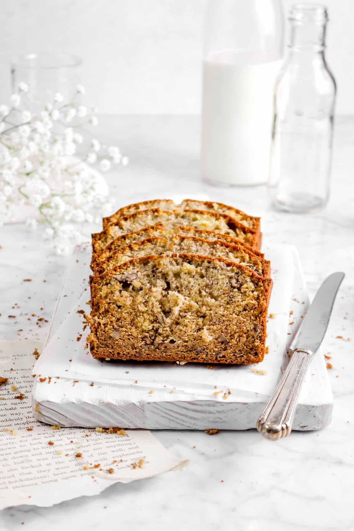 slices of banana bread on white board with crumbs, knife, book pages, flowers, and glasses