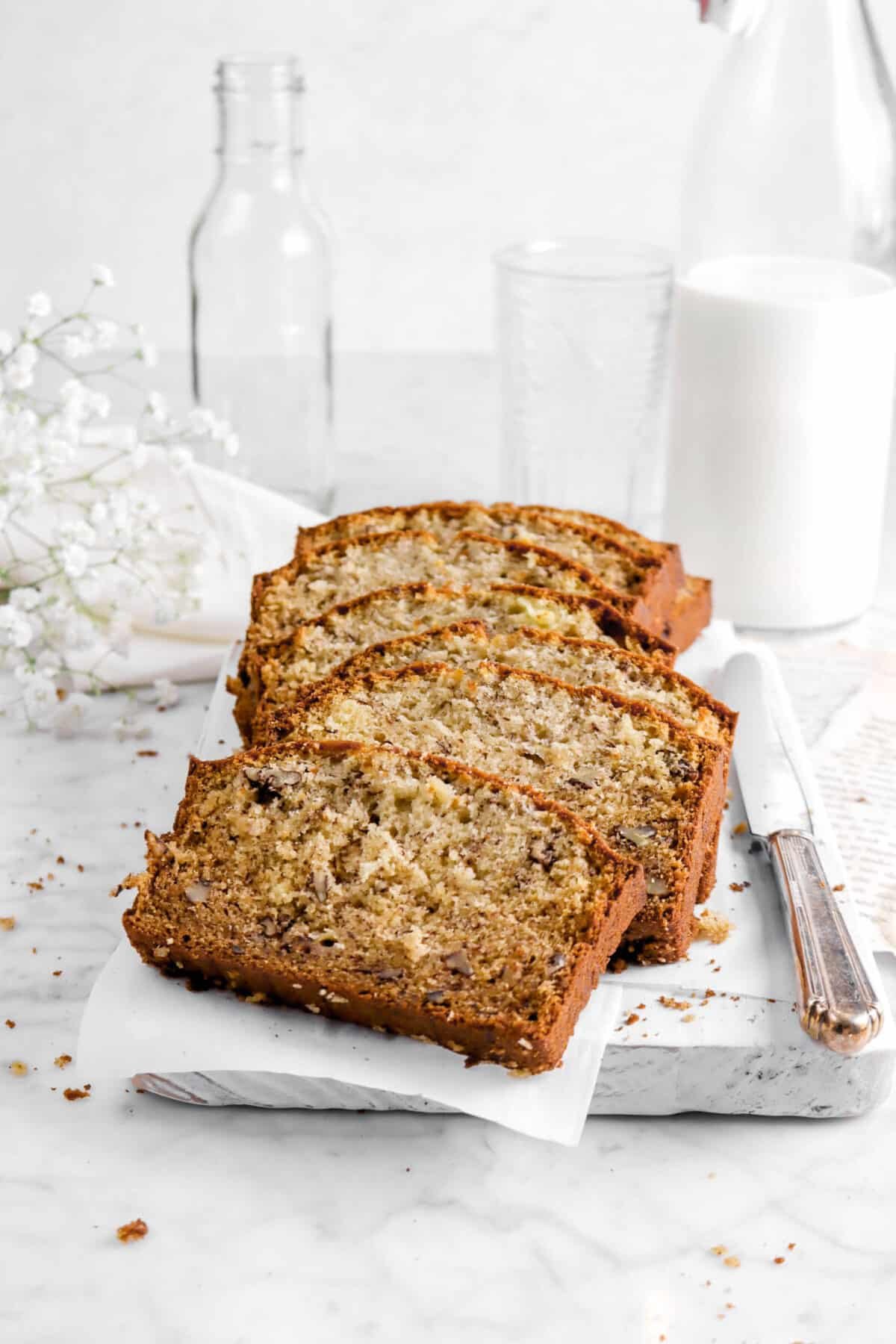 banana bread on white board with knife, milk, two glasses, napkin, and flowers behind