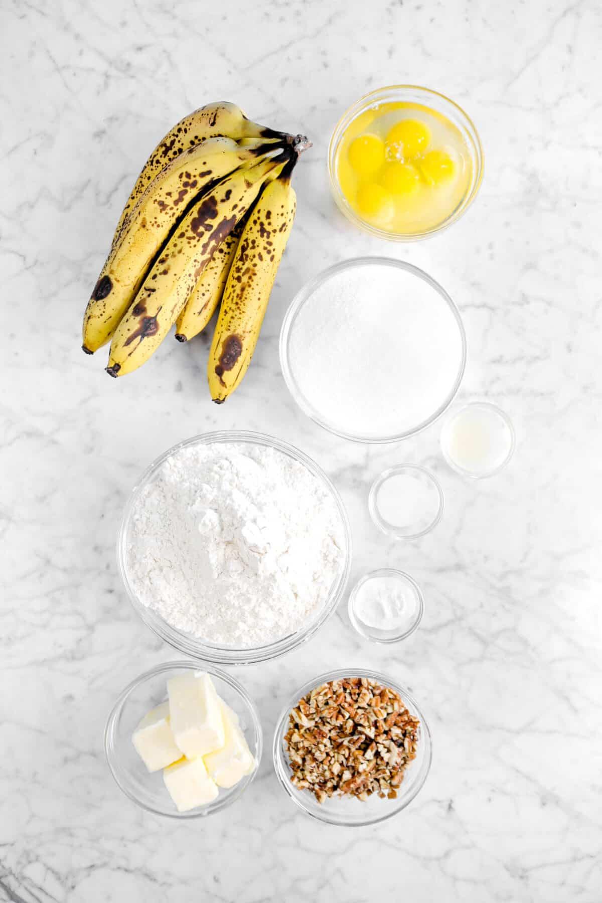 bananas, eggs, sugar, lemon juice, baking soda, salt, flour, chopped pecans, and butter on marble counter