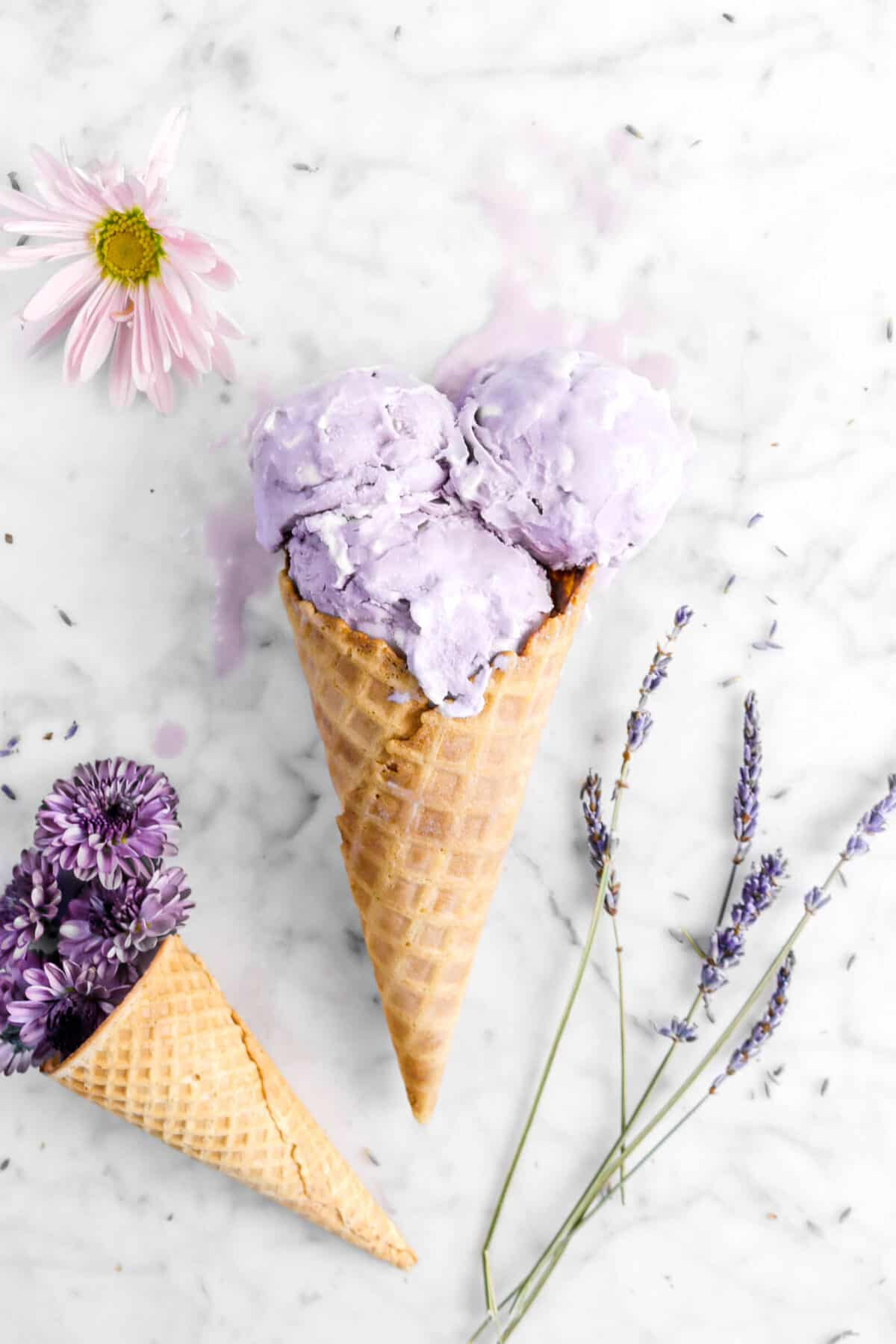 three scoops of ice cream in a cone with purple flowers and lavender