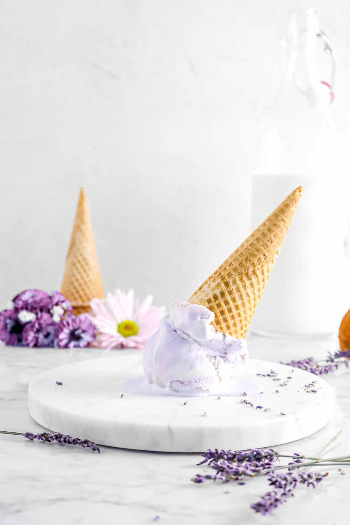 lavender ice cream upside with died lavender, with flowers and glass of milk