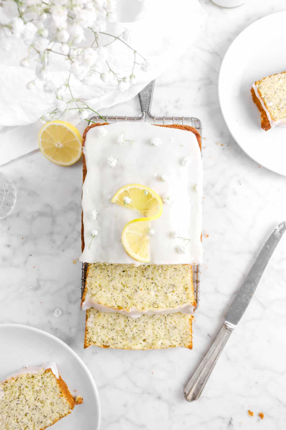 overhead shot of lemon poppy seed bread with glaze and lemon twist on top, two slices in front, and flowers