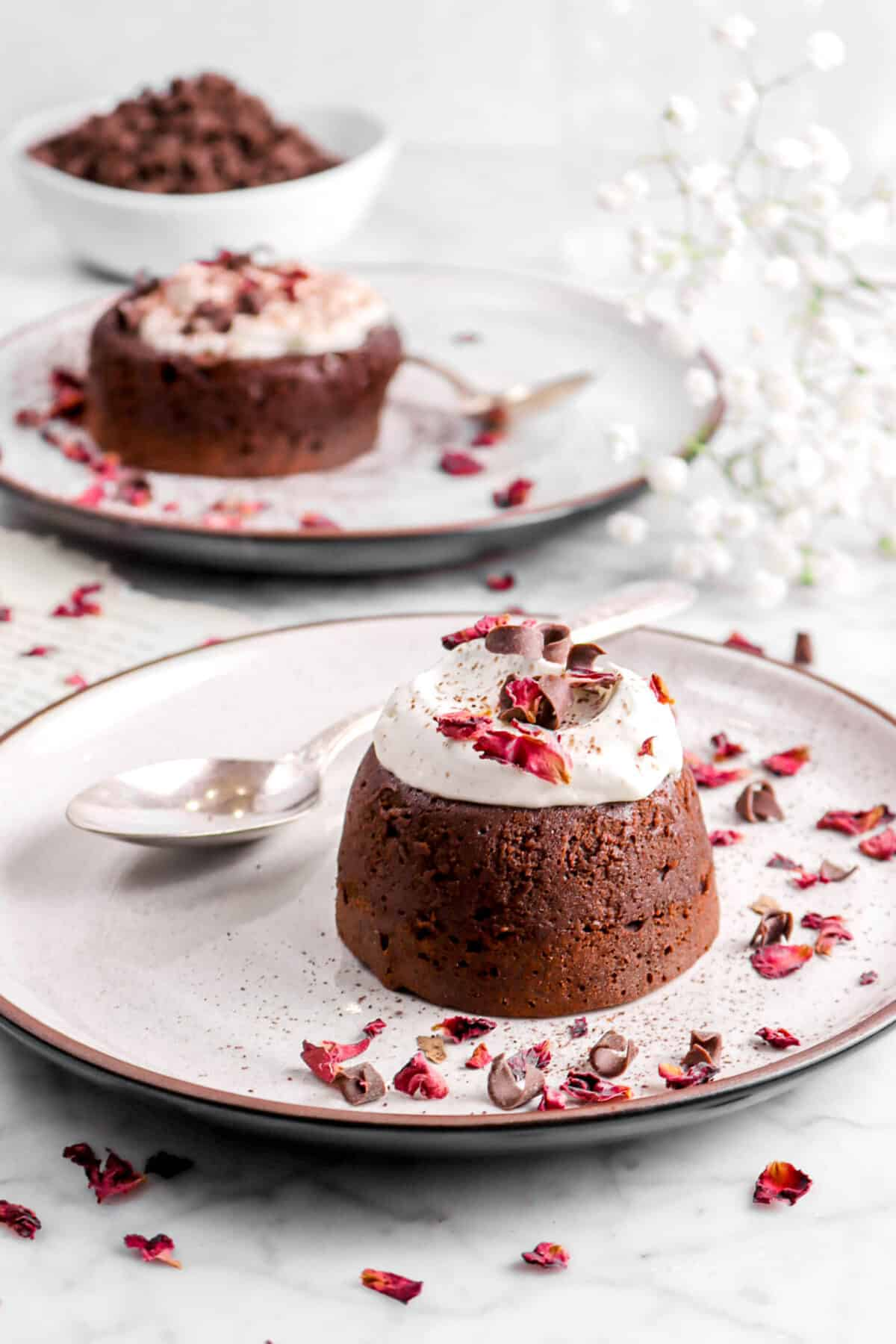 cake on plate with whipped cream and rose petals with another one behind