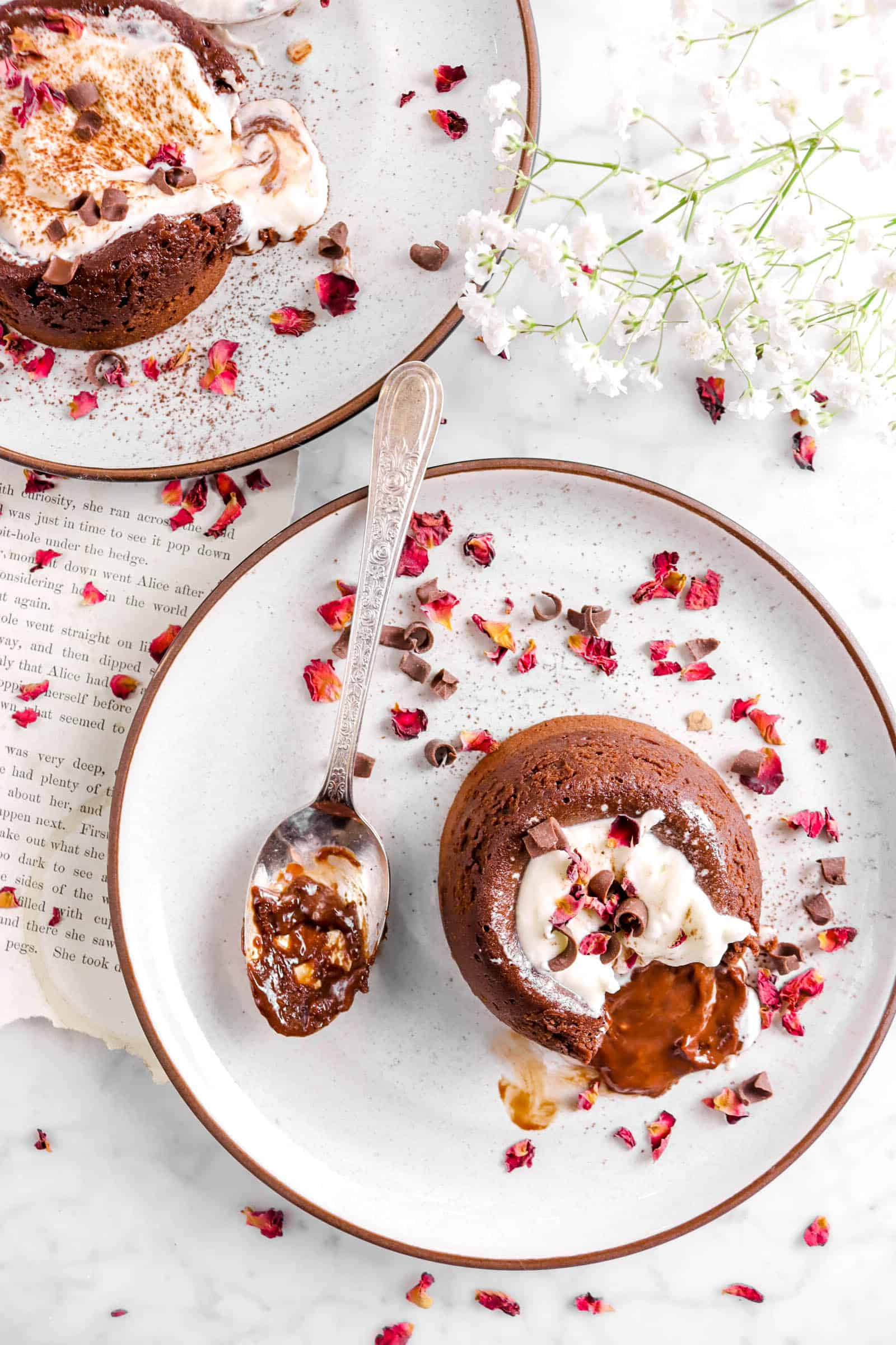 overhead shot of two chocolate lava cakes with a chocolate covered spoon, white flowers, and rose petals