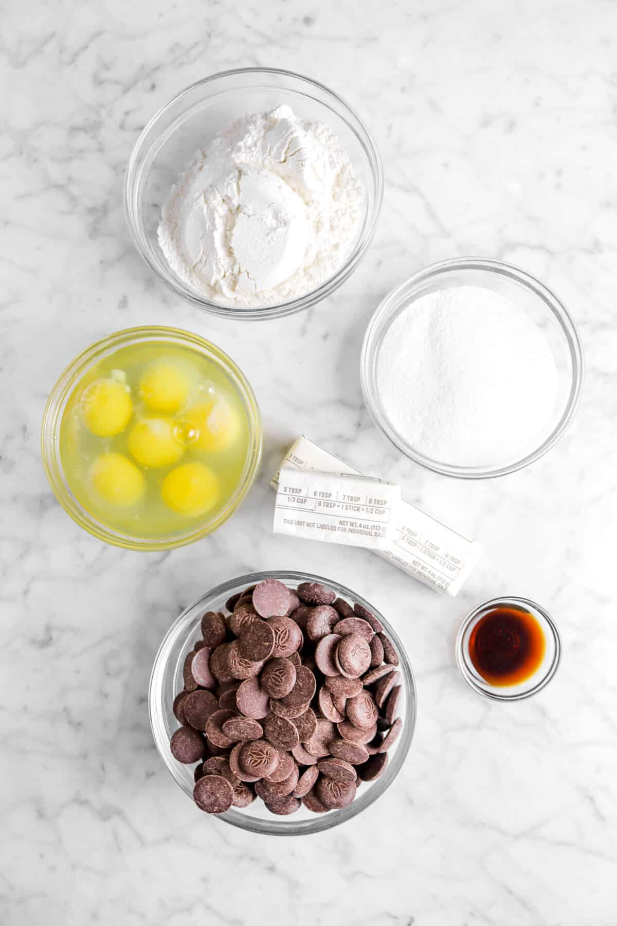 flour, sugar, eggs, butter, vanilla, and chocolate in glass bowls