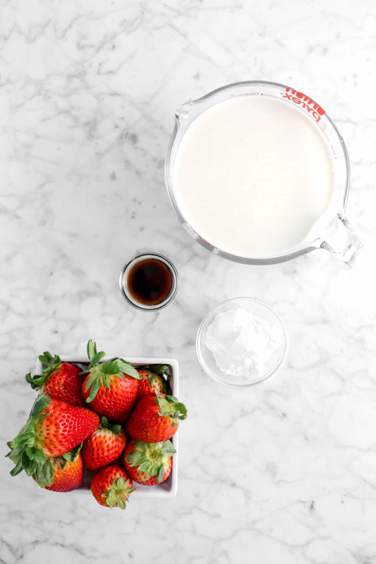 cream, vanilla, powdered sugar, and strawberries on marble counter