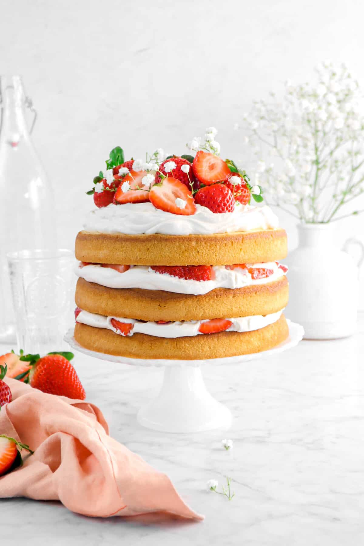 strawberry shortcake cake on white cake stand with pink napkin, flowers, and glasses behind
