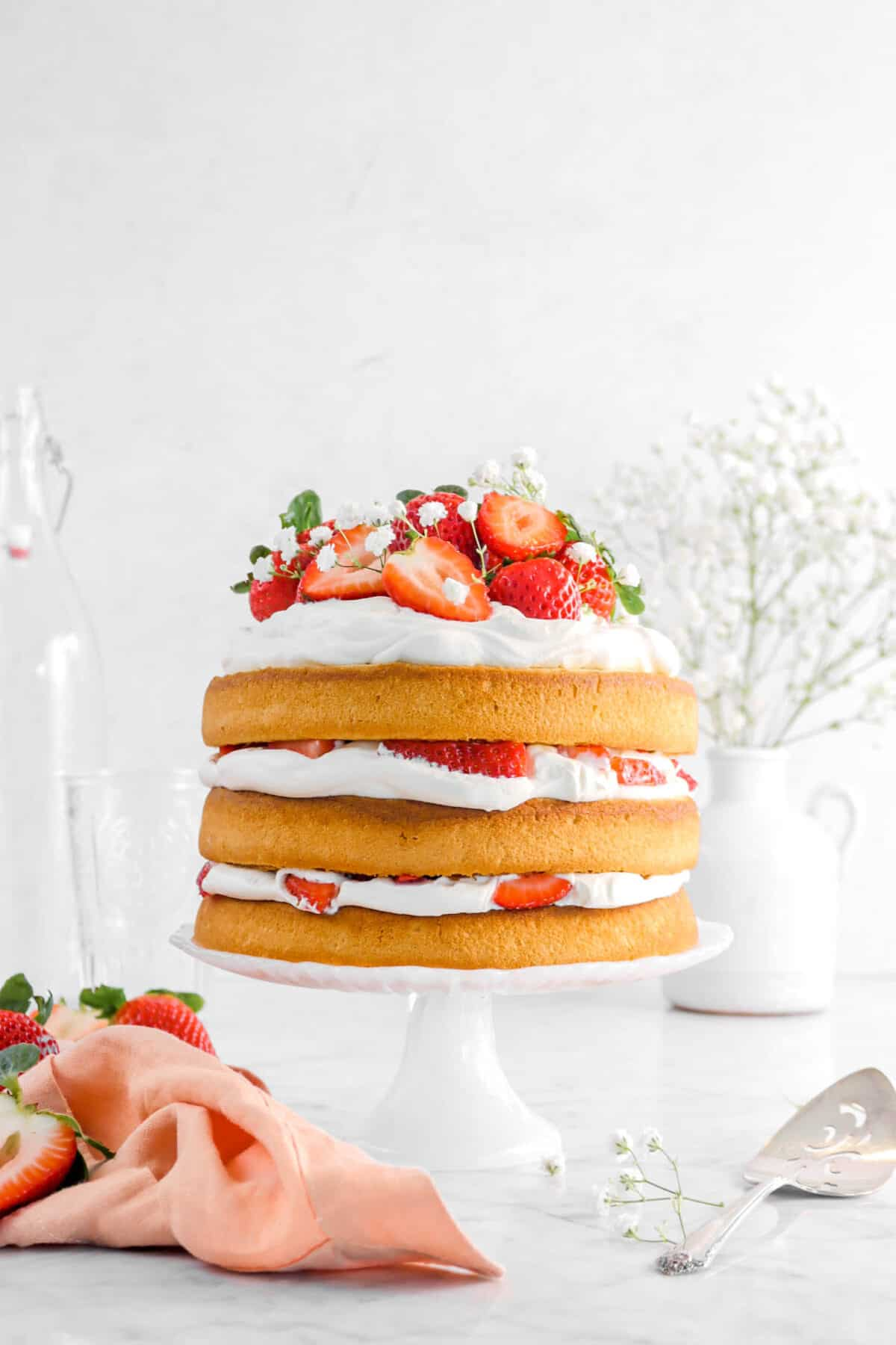 strawberry shortcake cake on white cake stand with strawberries, flowers, and a pink napkin
