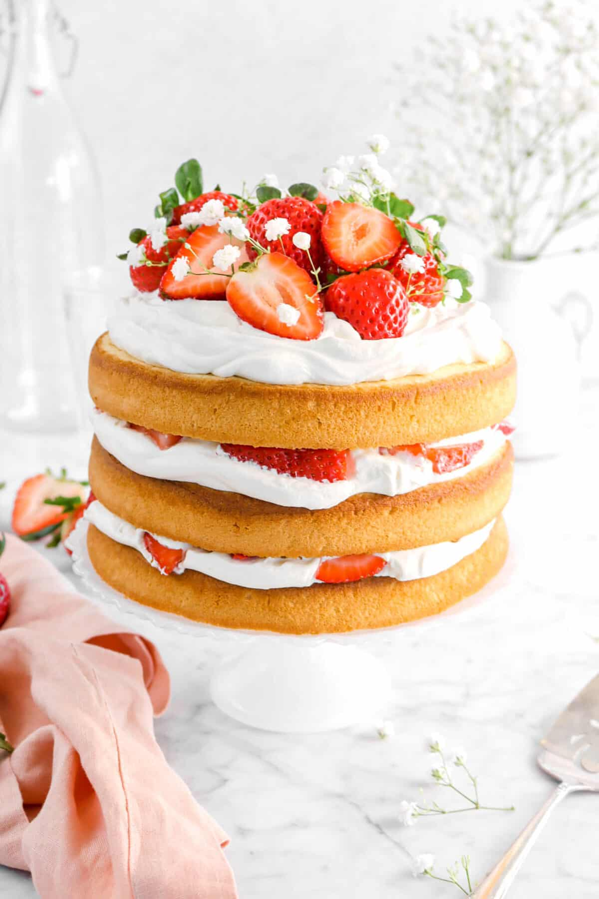 strawberry shortcake layer cake with pink napkin, flowers around, and glasses behind