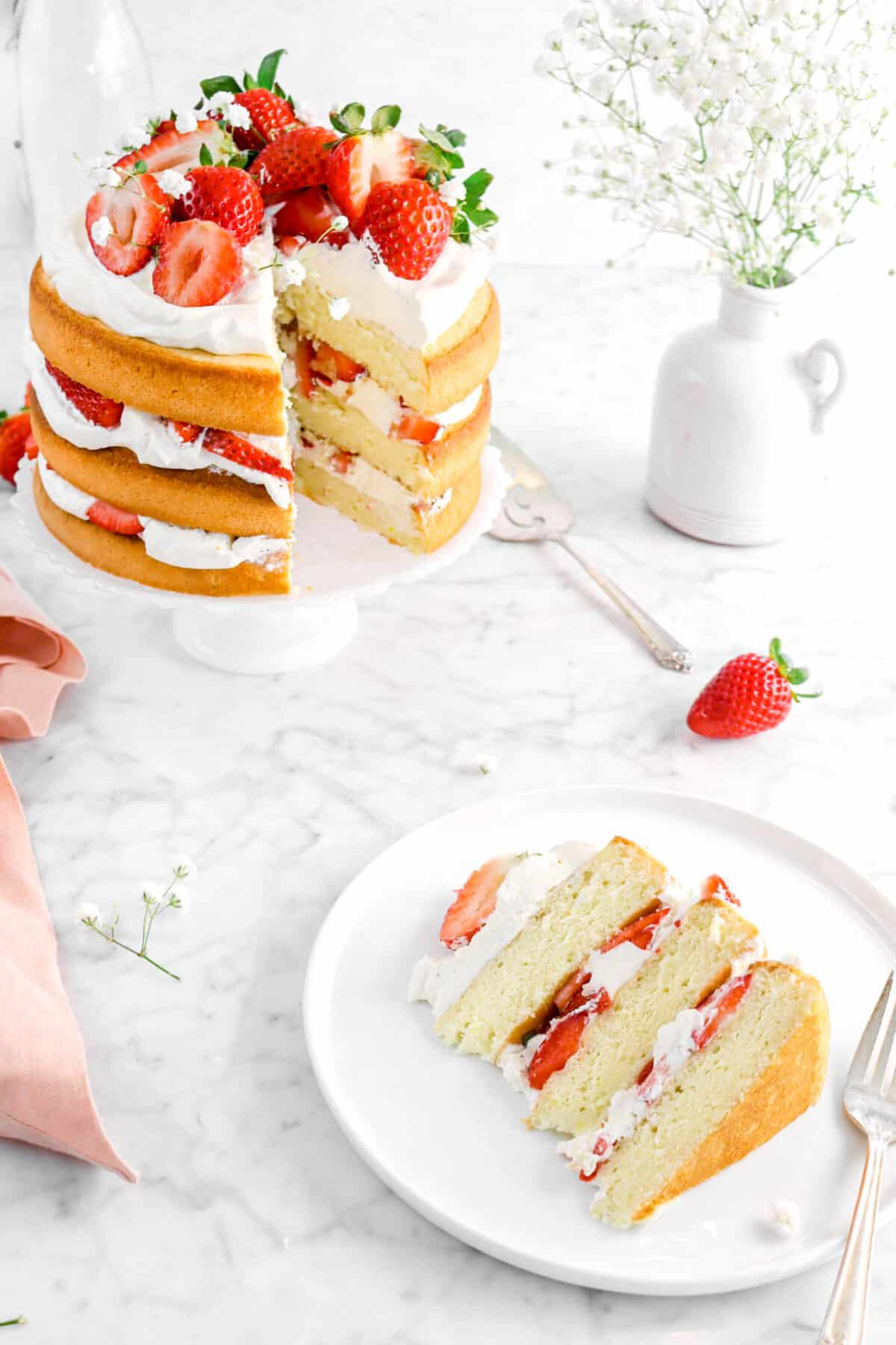strawberry shortcake cake slice on white plate with a fork, full cake beside, and white flowers