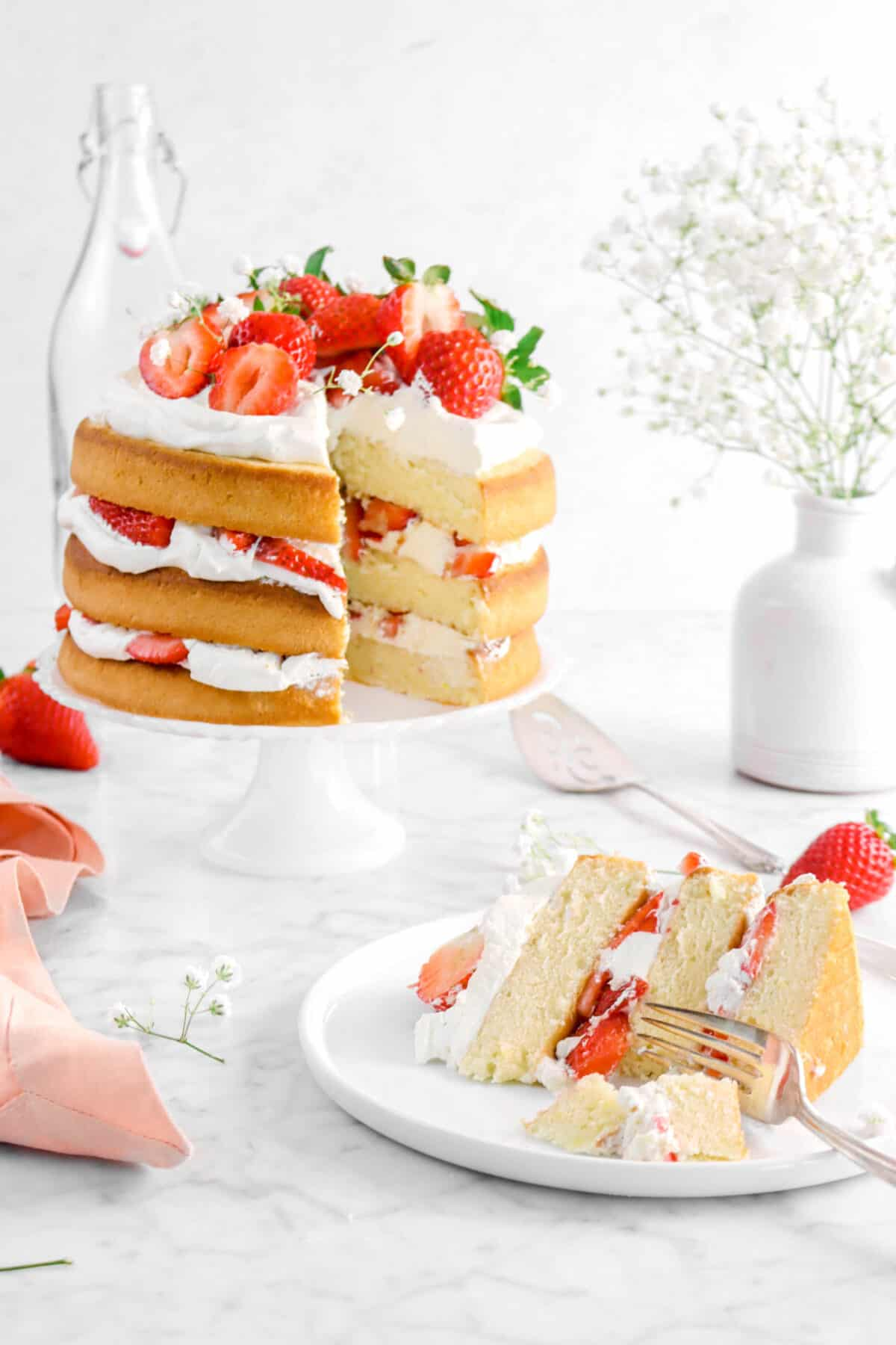 slice of strawberry shortcake layer cake being cut into with fork, full cake behind with jar of flowers