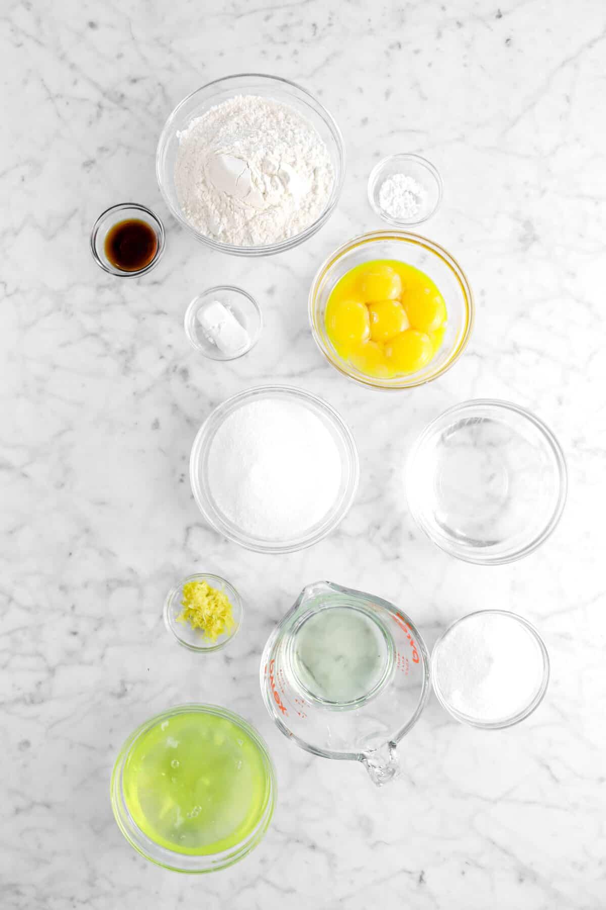 flour, cream of tartar, vanilla, baking powder, egg yolks, sugar, water, lemon zest, vegetable oil, and egg whites on marble counter