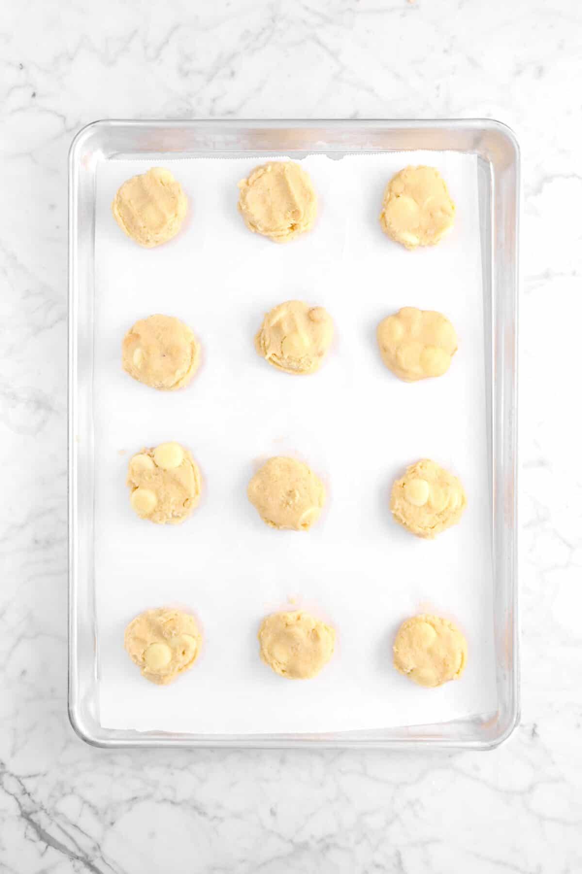 twelve unbaked cookies on a lined sheet pan