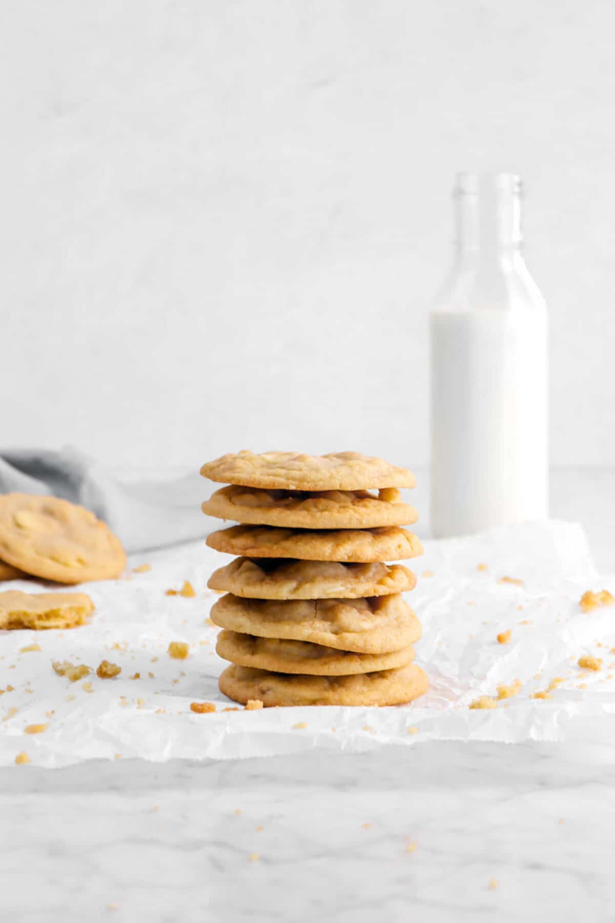 seven stacked cookies on parchment paper with cookie crumbs, a cookie behind, and a glass of milk